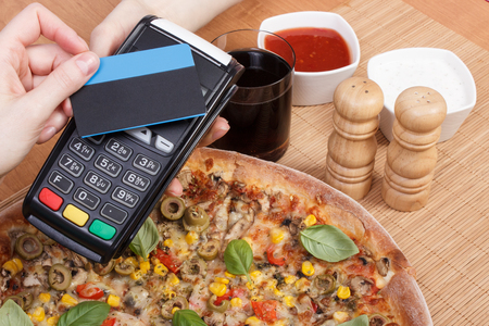 contactless: Using payment terminal with contactless credit card, cashless paying for vegetarian pizza in restaurant, finance and banking concept