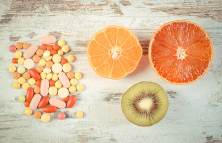 medical choice: Vintage photo, Fresh natural fruits and medical pills, tablets and capsules on rustic wooden background, choice between healthy nutrition and medical supplements, healthy lifestyle