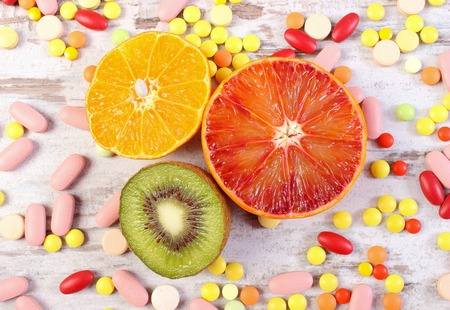 medical choice: Fresh natural fruits and medical pills, tablets and capsules on rustic wooden background, choice between healthy nutrition and medical supplements