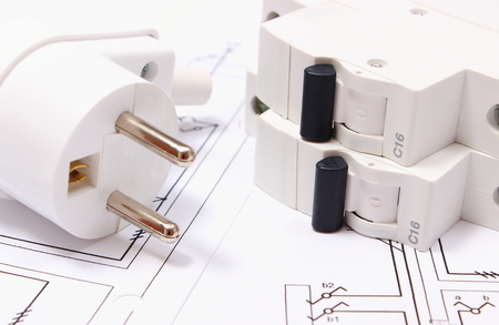 energy work: Electric plug and fuse lying on construction drawing of house, accessories for engineering work, energy concept Stock Photo