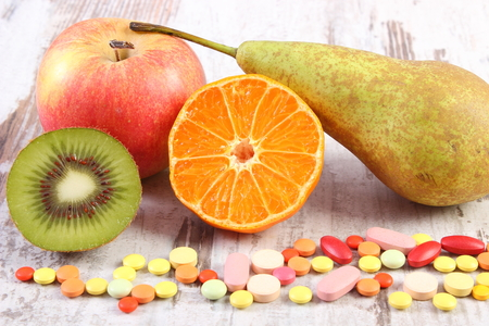 medical choice: Fresh natural fruits and medical pills, tablets and capsules on rustic wooden background, choice between healthy nutrition and medical supplements, healthy lifestyle