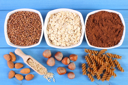 dietary fiber: Natural ingredients and products containing magnesium and dietary fiber, healthy food and nutrition, wholemeal pasta, buckwheat, oatmeal, cocoa, brown rice, almonds, hazelnut