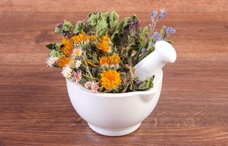 herbalism: Dried herbs and flowers in white mortar on rustic board, summer decoration, herbalism