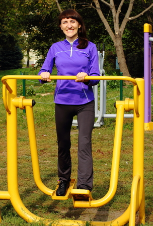 lower body: Brunette woman exercising lower body and legs on outdoor gym, concept of healthy and sporty lifestyle Stock Photo