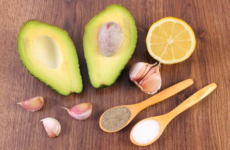 acids: Avocado with ingredients and spices to avocado paste or guacamole, garlic, lemon, concept of healthy food, nutrition and omega fatty acids