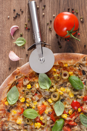pizza cutter: Pizza cutter and fresh baked vegetarian pizza with vegetable, ingredients and spices on rustic wooden background, italian cuisine, fast food Stock Photo