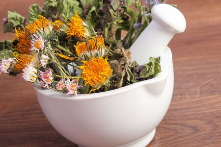 herbalism: Dried herbs and flowers in white mortar on rustic board, summer decoration, herbalism