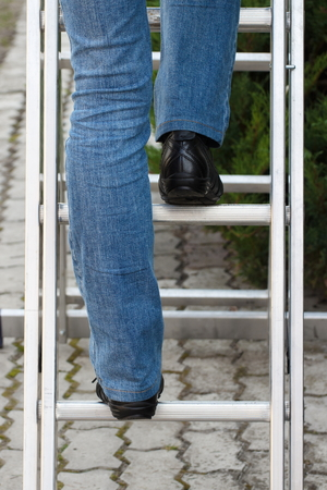 enters: Female worker climbing on aluminum ladder in garden, enters the ladder Stock Photo