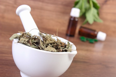 herbalism: Dried lemon balm in white mortar and medical capsules, choice between pills and alternative medicine, healthy lifestyle, herbalism Stock Photo
