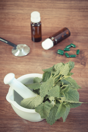 medical choice: Vintage photo, Fresh green lemon balm in white mortar, stethoscope and medical capsules, choice between pills and alternative medicine, healthy lifestyle, herbalism