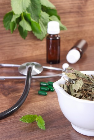 herbalism: Dried lemon balm in white mortar, stethoscope and medical capsules, choice between pills and alternative medicine, healthy lifestyle, herbalism