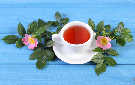 wild rose: Cup of hot tea with wild rose and blooming flowers on blue boards