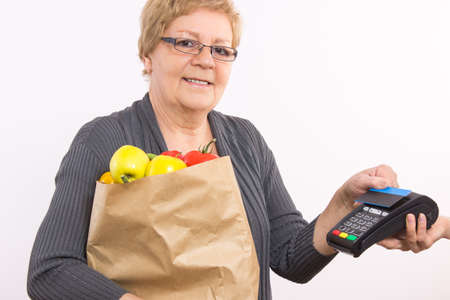 contactless: Elderly senior woman holding shopping bag and using payment terminal with contactless credit card, cashless paying for shopping, healthy nutrition in old age