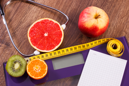bathroom scale: Electronic bathroom scale for weight of human body, tape measure and stethoscope with fruits, copy space for text on sheet of paper, healthcare, healthy lifestyles and slimming concept