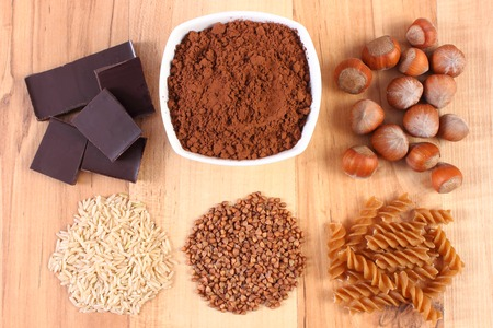 dietary fiber: Fresh, natural ingredients and products containing magnesium and dietary fiber, healthy food and nutrition, wholemeal pasta, buckwheat, brown rice, hazelnut, cocoa, chocolate Stock Photo