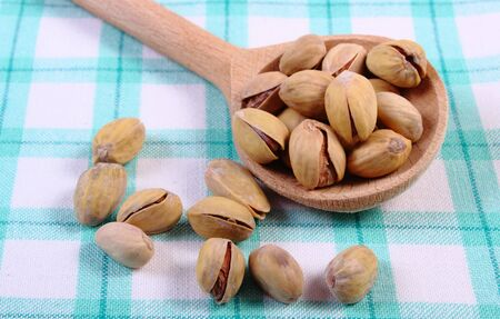 nutshells: Roasted pistachio nuts with wooden spoon on checkered tablecloth, healthy food and nutrition Stock Photo