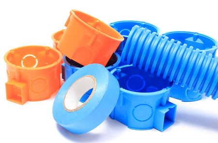 junction pipe: Heap of blue and orange electrical boxes with components for use in electrical installations, accessories for engineering jobs