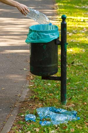 botar basura: Mano de la mujer de lanzar la botella de pl�stico en la basura vieja lata, el concepto de tirar basura y la protecci�n del medio ambiente Foto de archivo