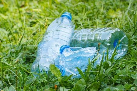 tirar basura: botellas aplastadas de pl�stico de agua mineral en la hierba en el parque soleado, concepto de tirar basura y la protecci�n del medio ambiente Foto de archivo