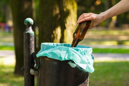 botar basura: Mano de la mujer que lanza botella de vidrio en la basura vieja lata, el concepto de tirar basura y la protección del medio ambiente Foto de archivo