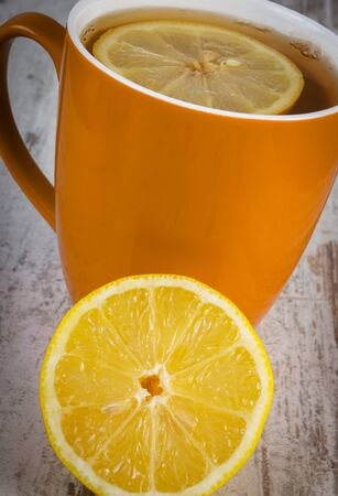warming therapy: Fresh lemon and cup of tea with lemon on old wooden table, healthy nutrition, strengthening immunity, alternative therapy