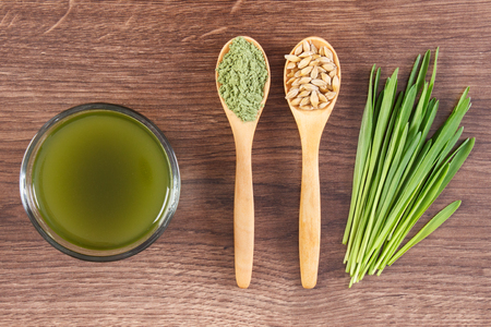 Barley grass, cup of beverage and grain with young powder on wooden spoon, healthy lifestyle, body detox
