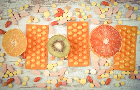 medical choice: Vintage photo, Fresh natural fruits and pills, tablets or capsules, choice between healthy nutrition and medical supplements Stock Photo