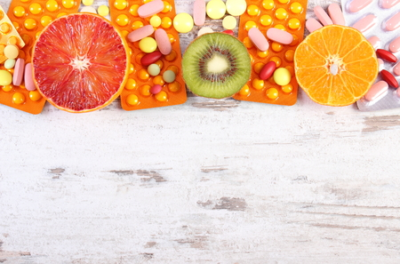 medical choice: Fresh natural fruits and pills, tablets or capsules, choice between healthy nutrition and medical supplements, copy space for text