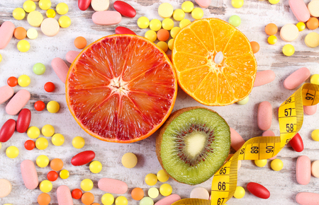 medical choice: Fresh fruits, tape measure, medical pills, tablets and capsules on rustic board, concept of slimming and choice between healthy nutrition and medical supplements