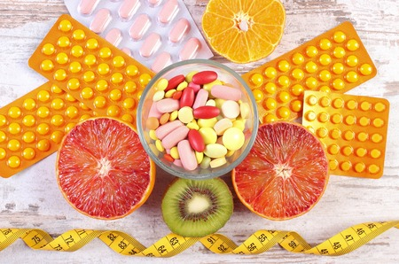 medical choice: Fresh natural fruits, tape measure, medical pills, tablets and capsules, concept of slimming and choice between healthy nutrition and medical supplements