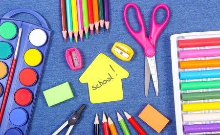 School supplies on jeans background, shape of building with word school, copy space for text or inscription, back to school concept