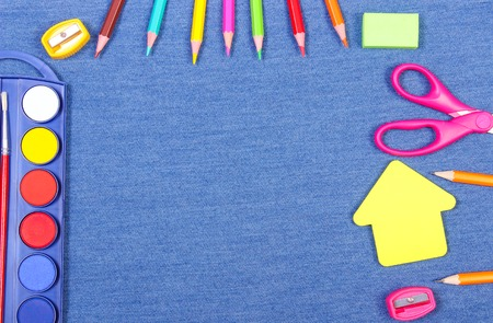 teaching crayons: Frame of school and office supplies on jeans background, shape of building, copy space for text or inscription, back to school concept