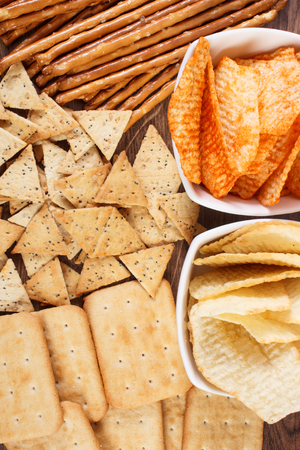 potato crisps: Heap of crunchy salted potato crisps, breadsticks and cookies, concept of restriction eating unhealthy and salted food