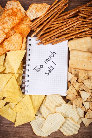 crisps: Inscription too much salt in notebook, crunchy potato crisps, breadsticks and cookies, concept of restriction eating unhealthy and salted food