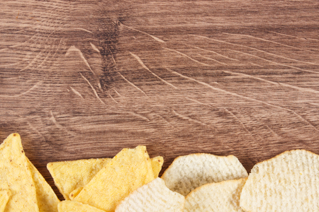 potato crisps: Potato crisps on rustic board, concept of restriction eating unhealthy and salted food, copy space for text or inscription Stock Photo