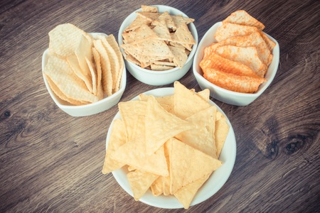 potato crisps: Vintage photo, Heap of crunchy salted potato crisps and cookies in bowls, concept of restriction eating unhealthy and salted food Stock Photo