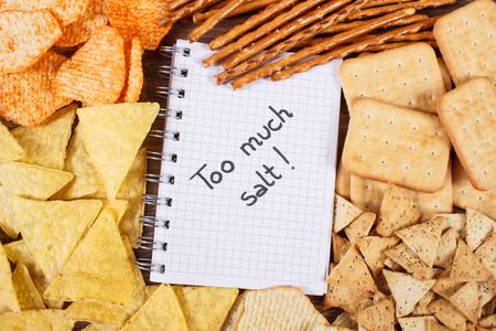 gressins: Inscription trop de sel dans le cahier, les chips croquantes, gressins et les cookies, concept de restriction manger des aliments malsains et salés