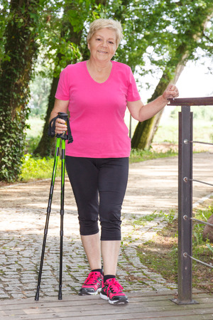 Elderly senior woman in sporty clothes practicing nordic walking in summer park, healthy sporty lifestyles on fresh air in old age