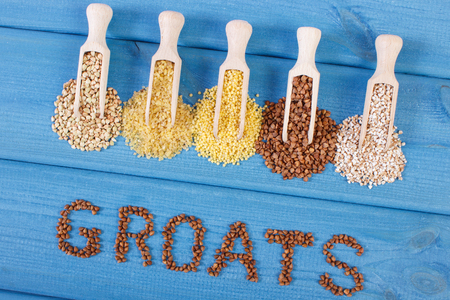 groats: Inscription groats and spoons with various groats on blue boards, concept of healthy food and nutrition Stock Photo