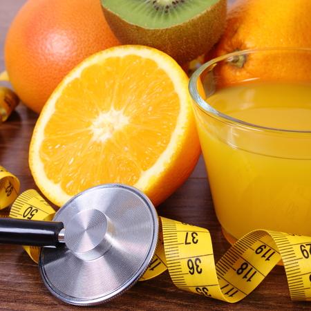inmunidad: M�dico estetoscopio y cinta m�trica con frutas maduras y vaso de jugo de a bordo, estilos de vida saludable y la nutrici�n inmunidad fortalecimiento
