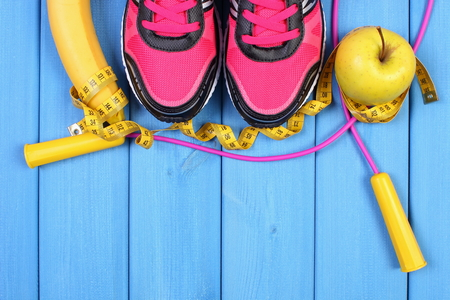ladylike: Sport shoes, fresh fruits and accessories for fitness on boards, healthy and active lifestyles, copy space for text or inscription