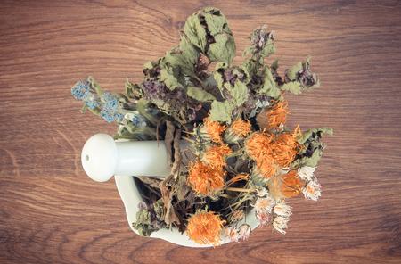 herbalism: Vintage photo, Dried herbs and flowers in white mortar on rustic board, summer decoration, herbalism