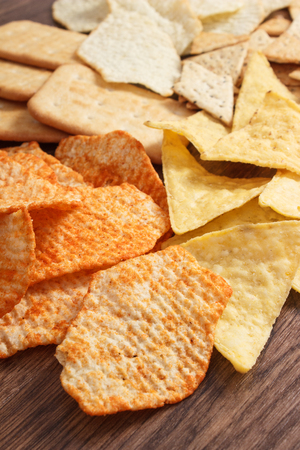 potato crisps: Heap of salted potato crisps with peppers and cookies on rustic board, concept of restriction eating unhealthy and salted food
