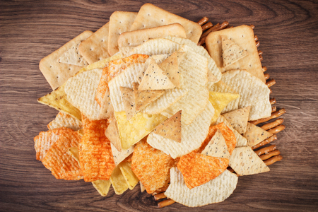 potato crisps: Heap of crunchy salted potato crisps, breadsticks and cookies on rustic board, concept of restriction eating unhealthy and salted food Stock Photo