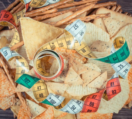 gressins: Vintage photo, Tape measure with crunchy potato crisps, cookies and breadsticks on rustic board, concept of slimming, restriction eating unhealthy and salted food Banque d'images