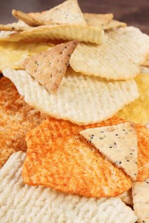 potato crisps: Heap of crunchy salted potato crisps and cookies on rustic board, concept of restriction eating unhealthy and salted food Stock Photo