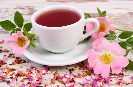wild rose: Cup of hot tea with wild rose, fresh blooming flowers and dried petals with tea grains on old wooden board Stock Photo