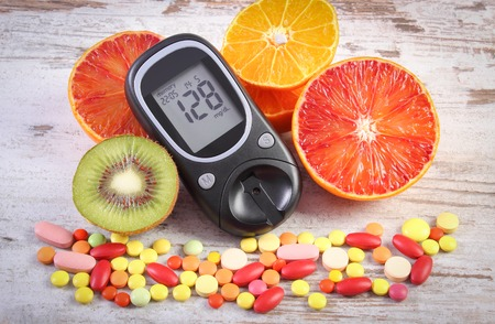 glucometer: Glucometer with result of measurement sugar level, fresh natural fruits and medical pills, tablets or supplements, concept of diabetes, healthy lifestyle and nutrition