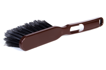 duties: New brown brush broom for cleaning on white background, concept of household duties