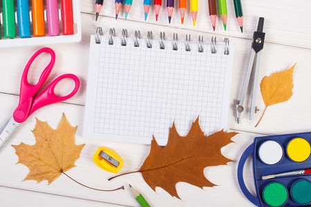 Office accessories and orange leaves on white boards, copy space for text in notepad, back to school in autumn concept